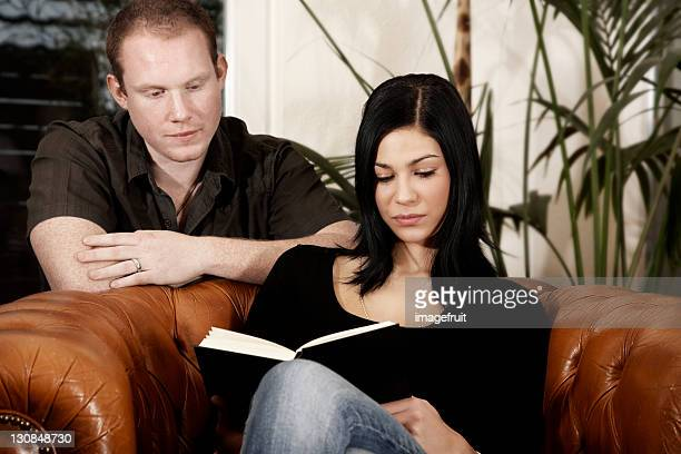 Young couple reading a book together