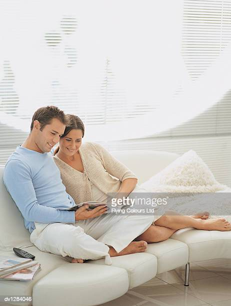 Young Couple Reading a Magazine Sitting on a Sofa in Their Sitting Room