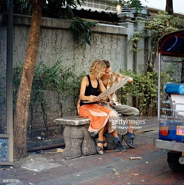 A young couple reading a map in Bangkok Thailand