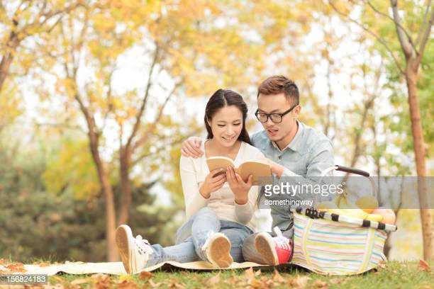 young couple reading book in park