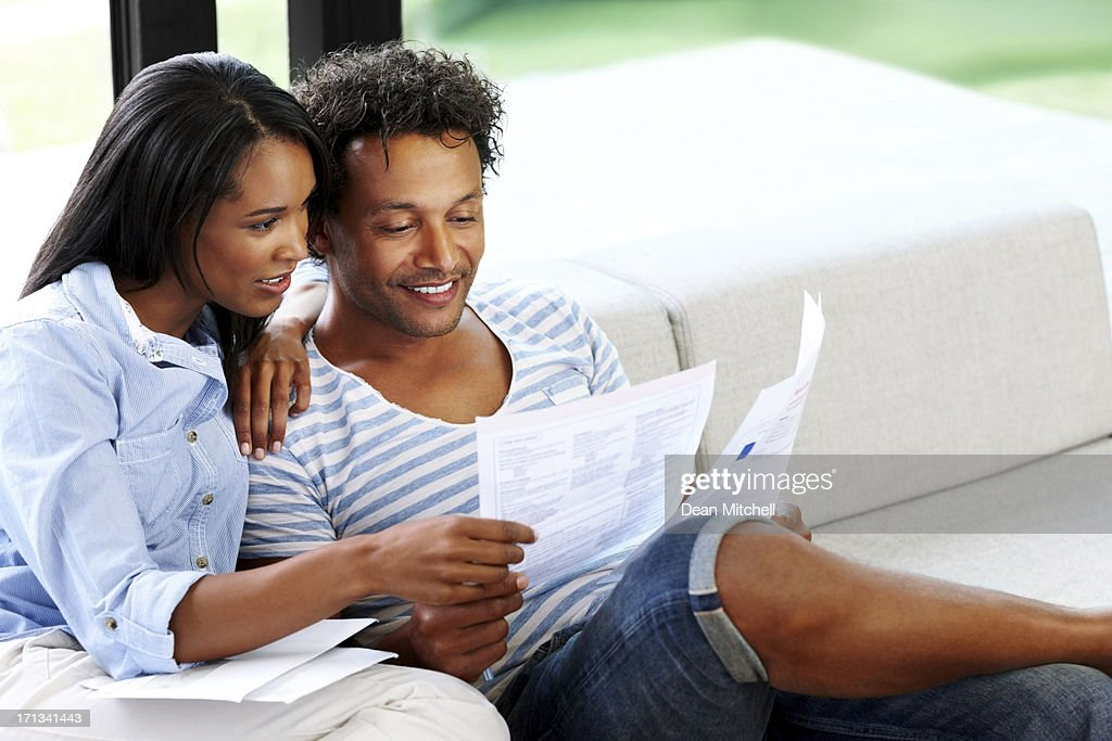 Young couple reading financial bill at home : Stock Photo