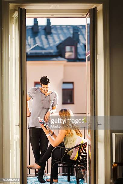 Young couple reading guidebook while planning vacations at balcony