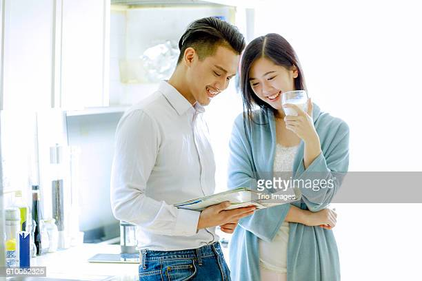 young couple reading magazine together in kitchen - glass magazine stock photos and pictures