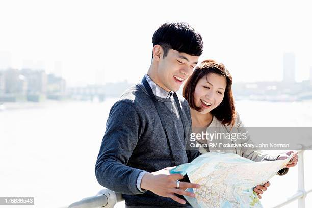 Young couple reading map and smiling