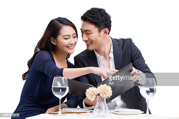 Young couple reading menu in restaurant