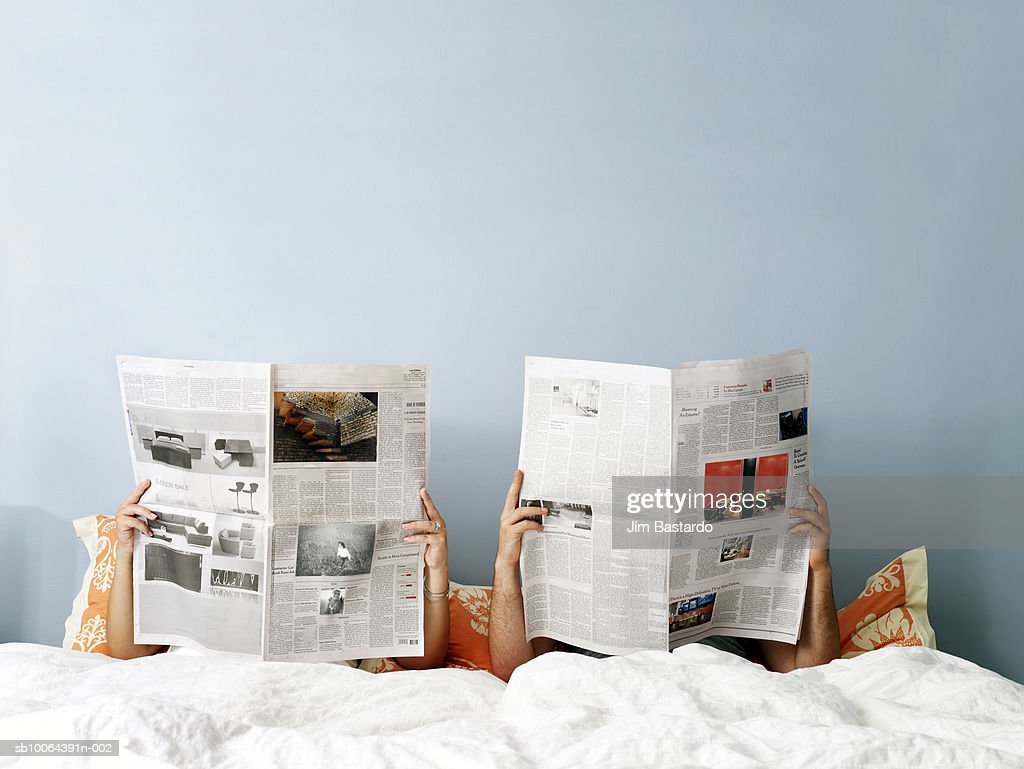 Young couple reading newspaper on bed : Stock Photo