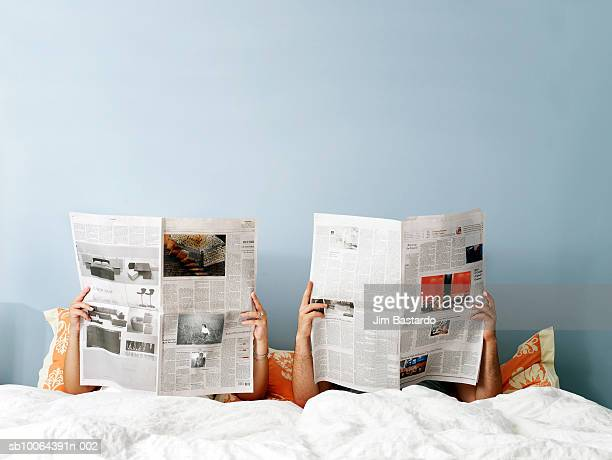 young couple reading newspaper on bed - newspaper stock pictures, royalty-free photos & images
