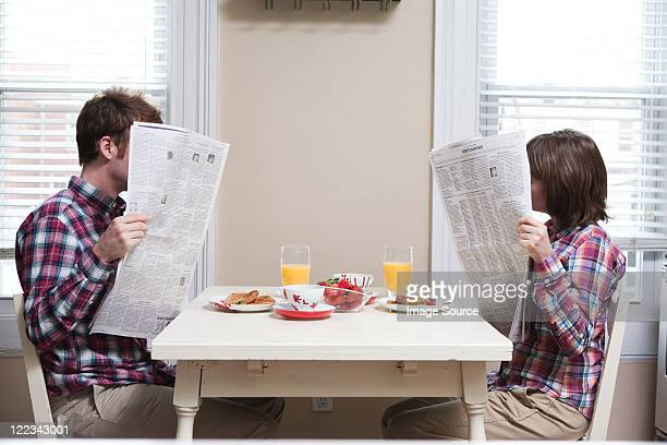 Young couple reading newspapers at kitchen table