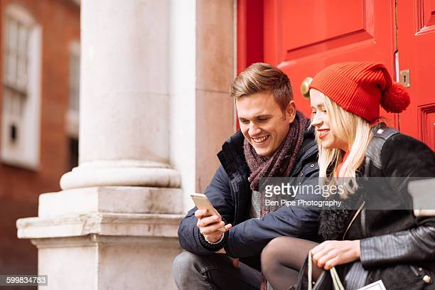 Young couple reading smartphone texts on doorstep, London, UK