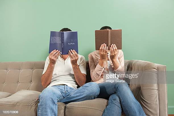 young couple reading with books obscuring faces - obscured face stock pictures, royalty-free photos & images