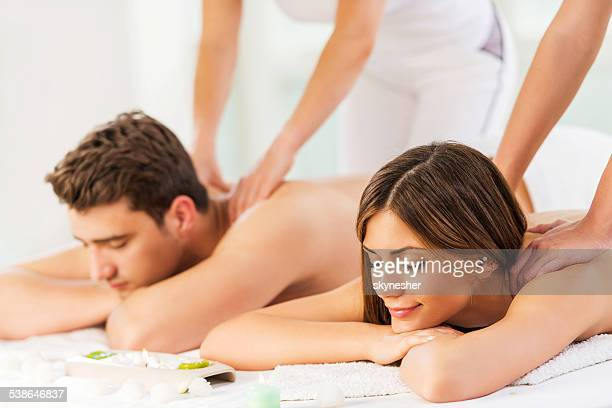 young couple receiving back massage. - massage stock photos and pictures