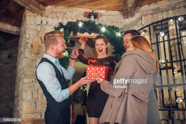 young couple receiving gift from guests - hello december stock pictures, royalty-free photos & images