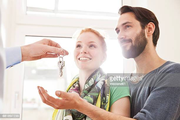 young couple receiving house key from real estate agent - house key stock photos and pictures