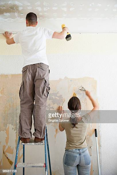 young couple redecorating - scraping stock photos and pictures