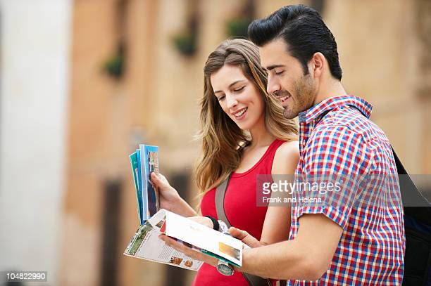 Young couple referring to guidebook