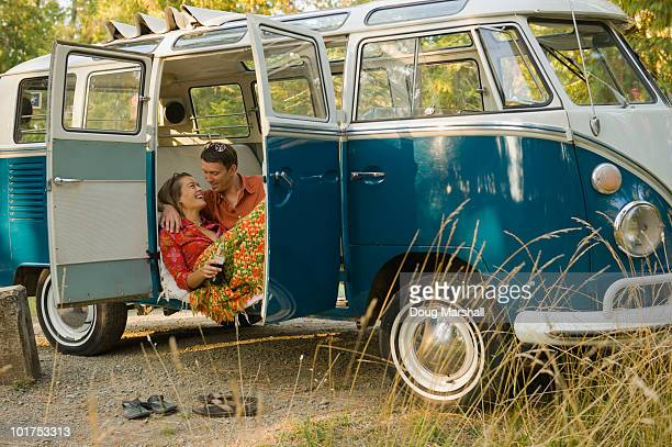A young couple relax inside a classic van.
