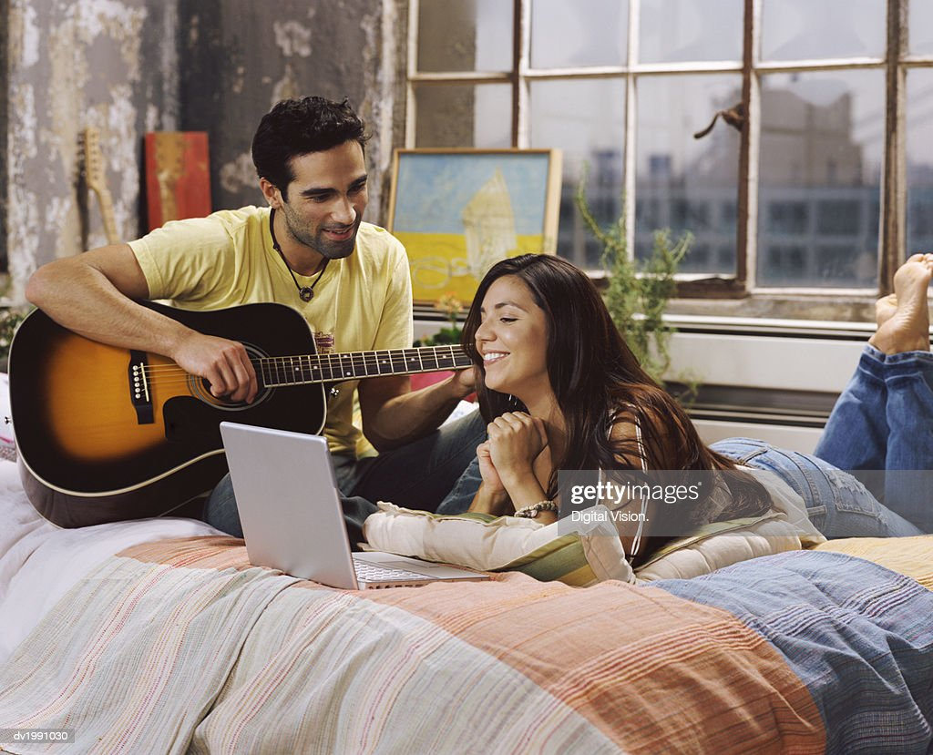Young Couple Relax on a Bed in Their Apartment, the Woman Using a Laptop and the Man Playing a Guitar : Stock Photo