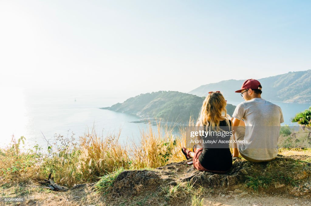 Young couple relax, on hillside above sea : Stock Photo
