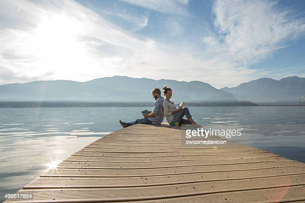 Young couple relax on lake pier with book,digital tablet
