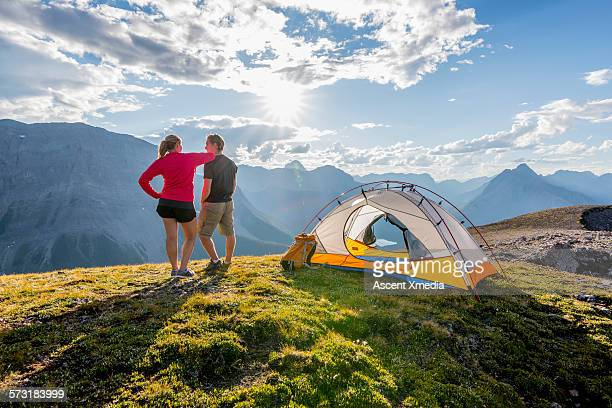 Young couple relax on ridge crest, beside tent