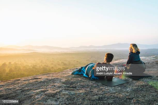young couple relax on rocky crest above jungle, sunrise - sigiriya stock photos and pictures