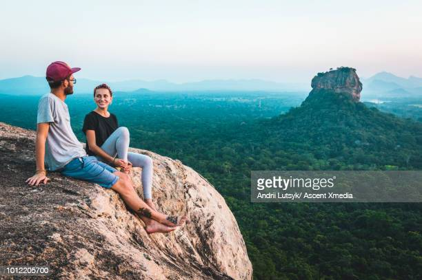 young couple relax on rocky crest above jungle, sunrise - mountain ridge stock pictures, royalty-free photos & images