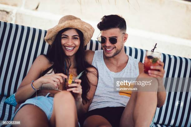 young couple relaxing and drinking cocktails at summer beach bar - cocktail party stock pictures, royalty-free photos & images