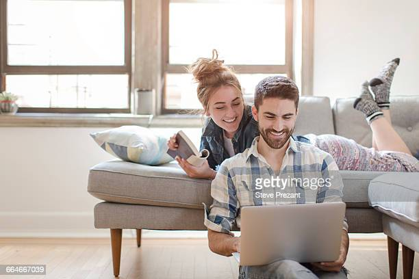 young couple relaxing at home, looking at laptop - young couple stock pictures, royalty-free photos & images