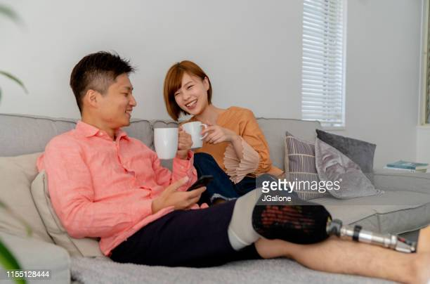 young couple relaxing at home - disability collection stock pictures, royalty-free photos & images