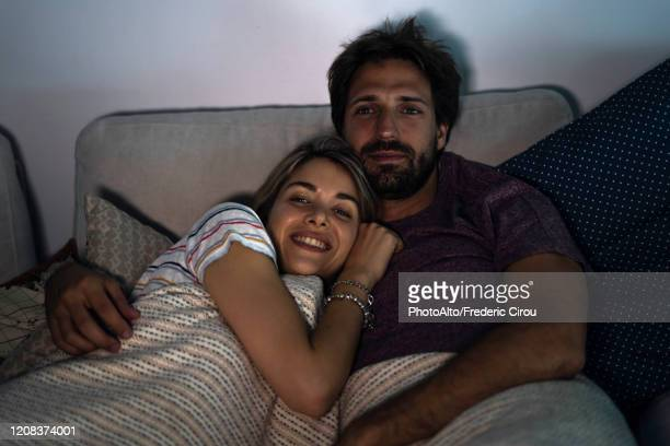 young couple relaxing at home - fernseher stock-fotos und bilder