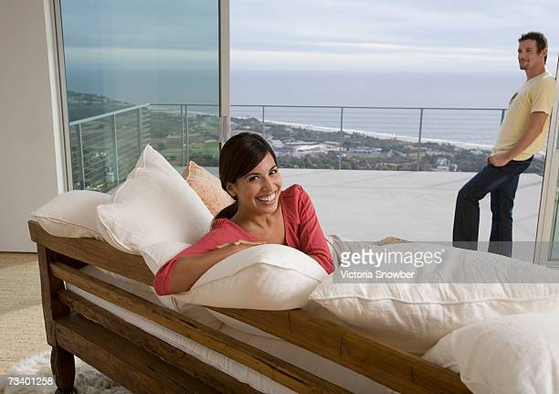 Young couple relaxing at home, view of ocean in background
