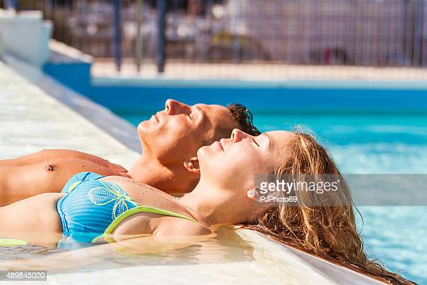 Young couple relaxing at swimming pool
