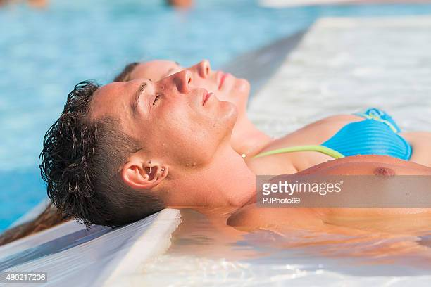 young couple relaxing at swimming pool - pjphoto69 stock pictures, royalty-free photos & images