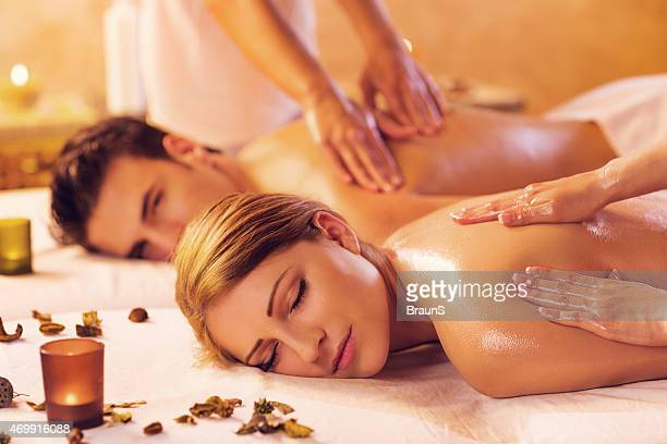 Young couple relaxing during a back massage at the spa.