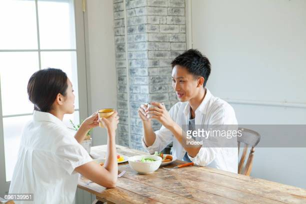 Young couple relaxing, having hot drink at table