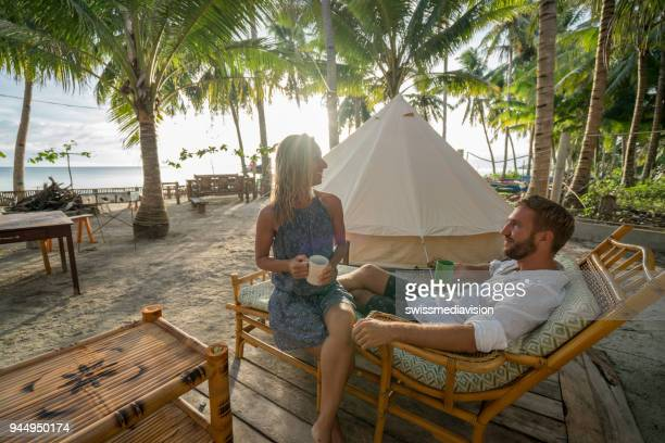 young couple relaxing in glamping campground in tropical scenery - heterosexual couple stock pictures, royalty-free photos & images