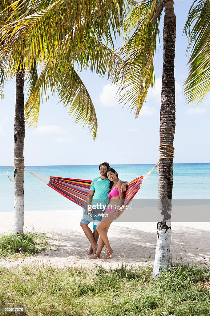 Young couple relaxing in hammock on beach : Stock Photo