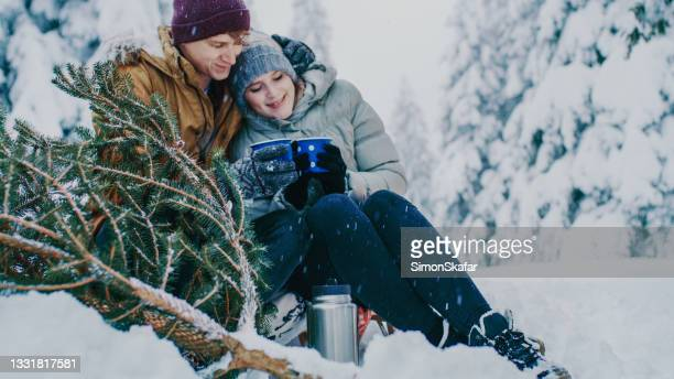 young couple relaxing in snow covered forest - moment of silence stock pictures, royalty-free photos & images