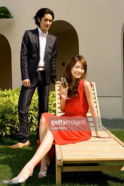 Young couple relaxing in the courtyard, woman sitting on deck chair with champagne