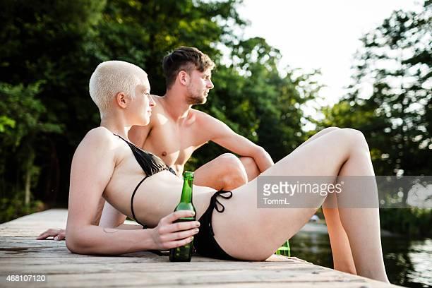 Junges Paar entspannenden auf einer Anlegestelle am Lake