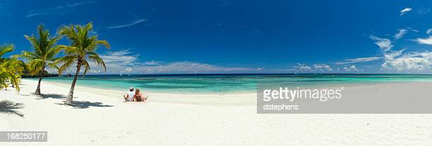 young couple relaxing on beach - panoramic stock pictures, royalty-free photos & images