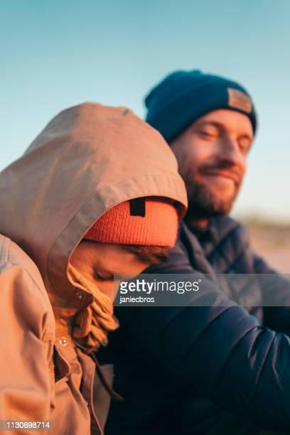 junges ehepaar entspannt sich am strand. frühling - kieferngewächse stock-fotos und bilder