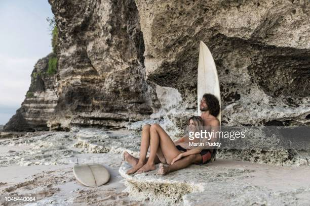 young couple relaxing on beach with surfboards