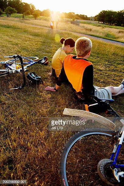 Young couple relaxing on grass in park, bikes lying on sides