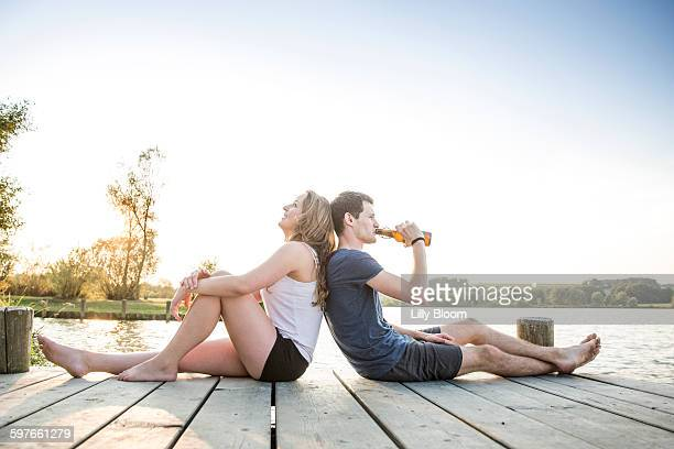 Young couple relaxing on jetty, sitting back to back