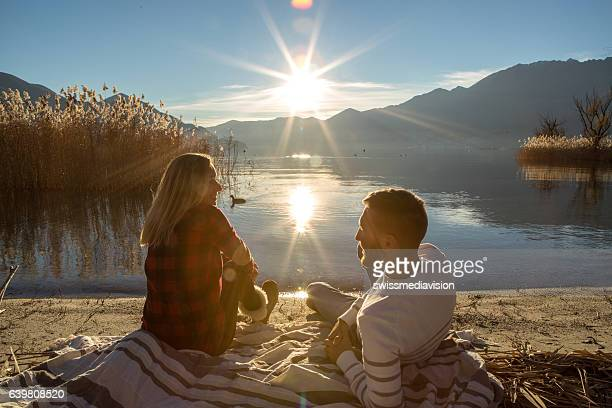 Young couple relaxing on lake beach