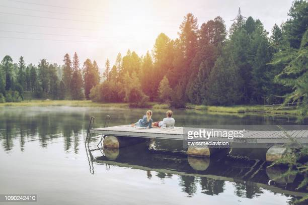 young couple relaxing on lake pier on overcast day enjoying nature and green environment - jetty stock pictures, royalty-free photos & images