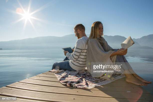 Young couple relaxing on lake pier