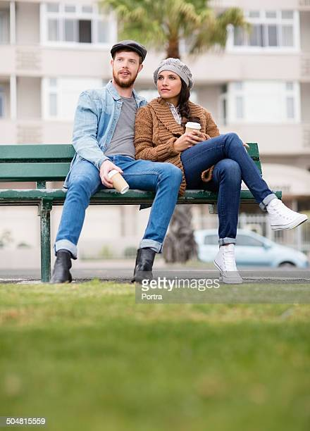Young couple relaxing on park bench