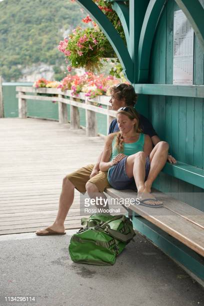 young couple relaxing on pier bench, lake annecy, annecy, rhone-alpes, france - annecy photos et images de collection